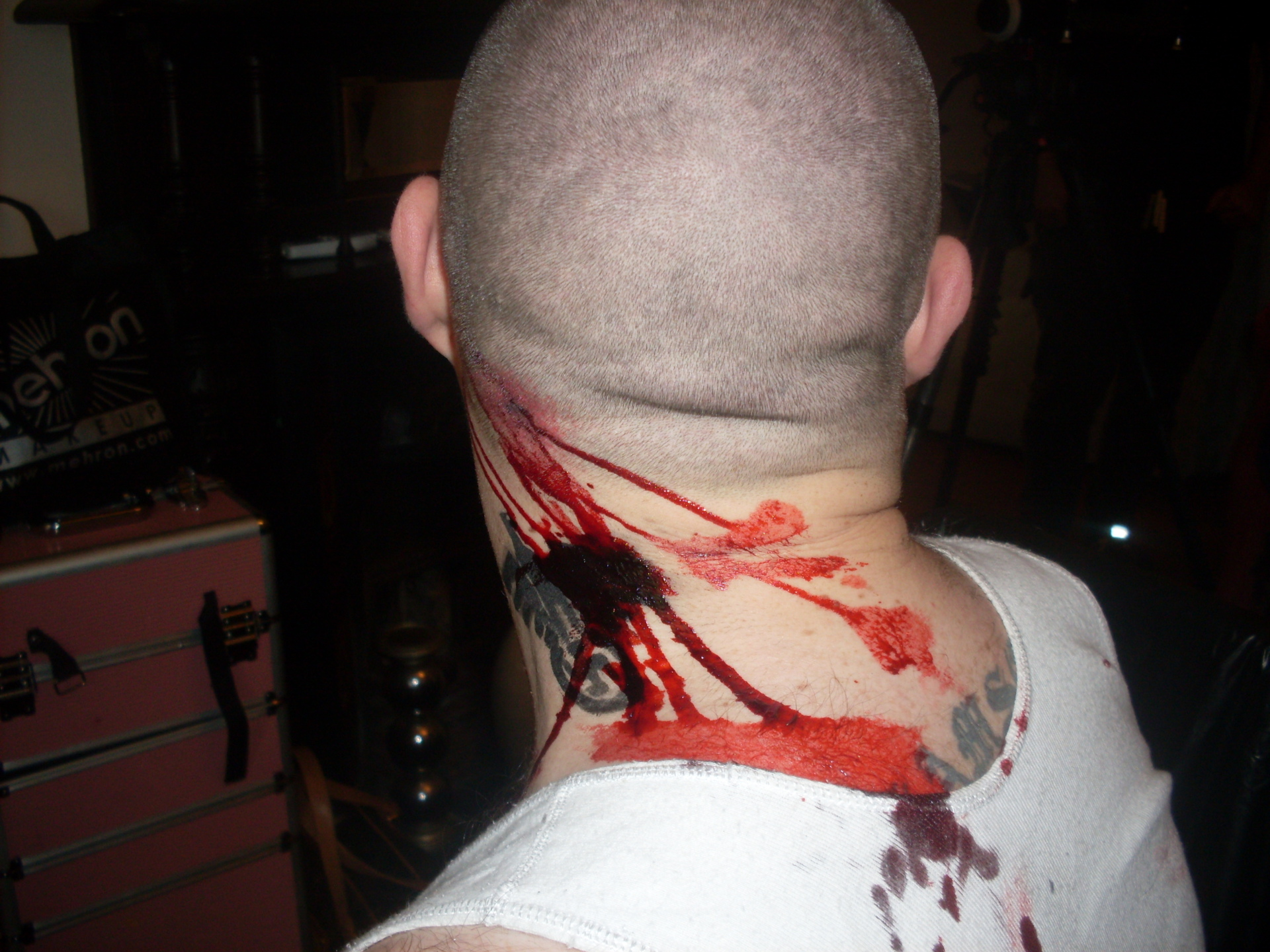 side of mans neck with gunshot wound and blood